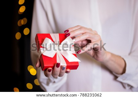 girl holding beautiful  gift for the day valentines day. red box and white bow and bokeh in the background #788231062