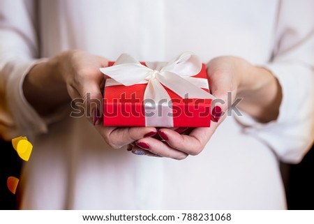 girl holding beautiful  gift for the day valentines day. red box and white bow and bokeh in the background #788231068