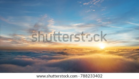 Beautiful aerial view above clouds with sunset. Airplane view #788233402