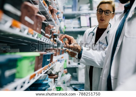 Two pharmacists checking inventory at hospital pharmacy. Hospital staff stocktaking in drugstore. #788251750