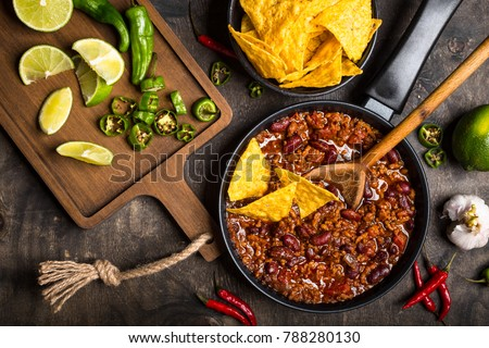 Chili con carne in frying pan on dark wooden background. Ingredients for making Chili con carne. Top view. Chili with meat, nachos, lime, hot pepper. Mexican/Texas traditional dish Chili con carne  #788280130