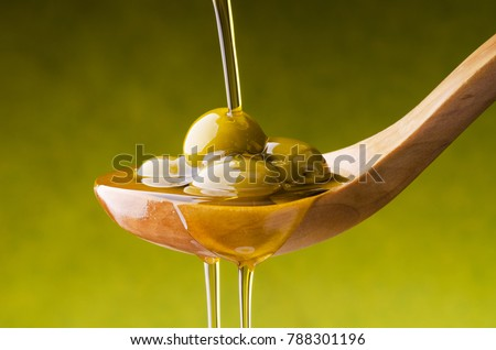extra virgin olive oil flows on a wooden bowl full of green olives #788301196
