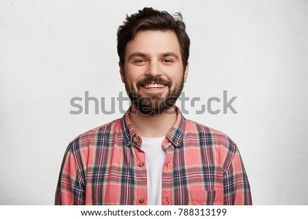 Smiling bearded young male model rejoices coming weekends, dressed casually, isolated over white background. Positive pleased student being in good mood after successfully passed exams at college #788313199
