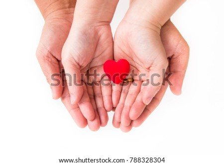 Women's and men's hand giving red heart on white background. Hands of lovers with red heart in the middle. #788328304