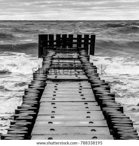 Concrete pier with wavy sea, black and white photo