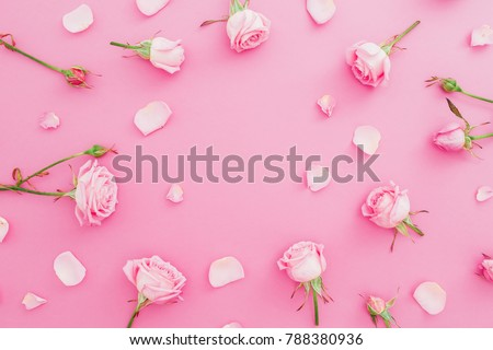 Floral frame made of roses flowers and petals on pink background. Flat lay, Top view. Valentines day background