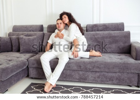 Loving young couple in white clothes hugging and relaxing on sofa at home #788457214