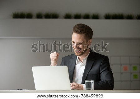 Happy young businessman in suit looking at laptop excited by good news online, lucky successful winner man sitting at office desk raising hand in yes gesture celebrating business success win result Royalty-Free Stock Photo #788459899