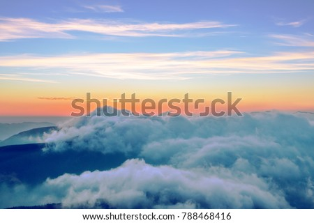 Majestic mountains sunrise with ground covered by clouds and luminous colors of sky on horizon #788468416