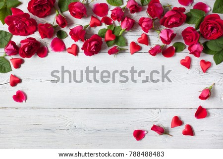 Roses and red hearts on a wooden background #788488483