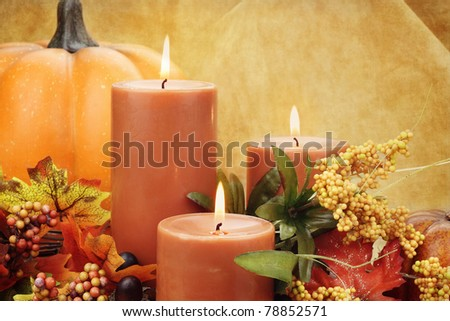 Lit candles surrounded by autumn decorations. Copy space available.