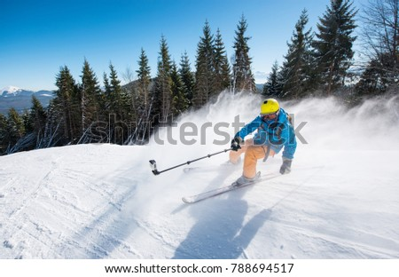 Action shot of professional skier taking selfies photo with a camera on selfie stick while skiing on fresh powder snow in the mountains at the winter resort Bukovel active lifestyle sport concept #788694517