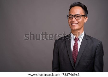 Studio shot of young handsome Indian businessman wearing suit with eyeglasses against gray background #788746963