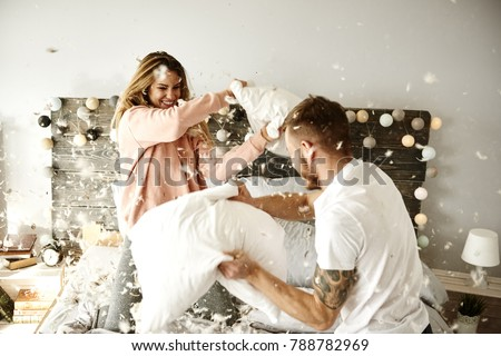 Couple having a fun while pillow fight #788782969
