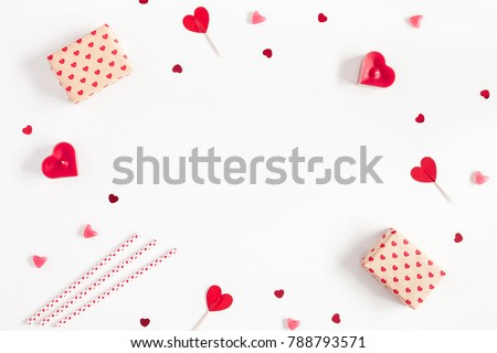 Valentine's Day. Frame made of gifts, candles, confetti on white background. Valentines day background. Flat lay, top view, copy space.