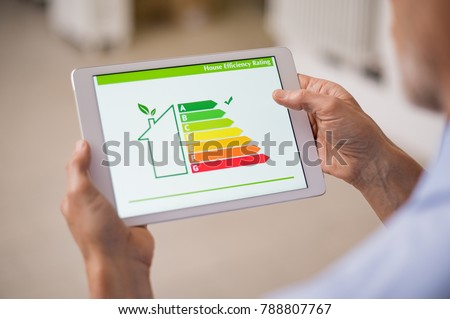 Hand holding digital tablet and looking at house efficiency rating. Detail of house efficiency rating on digital tablet screen. Concept of ecological and bio energetic house. Energy class. #788807767