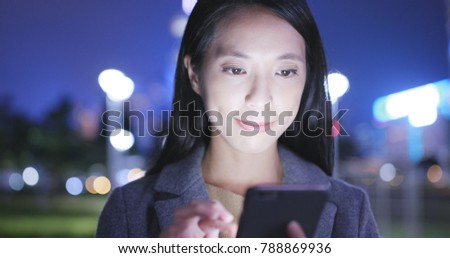 Young Woman look at mobile phone in city at night  #788869936