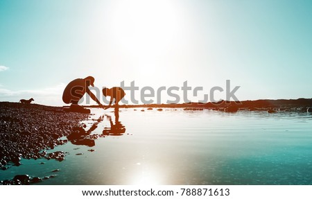 Silhouette of father and son playing on the beach at the sunset time - People having fun on summer vacation with their dog - Love, fatherhood and family concept #788871613