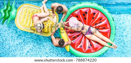 Happy friends having cheering with cocktails in swimming pool party - Young people enjoying summer holidays vacation in tropical hotel resort - Travel, holidays, youth and friendship concept #788874220