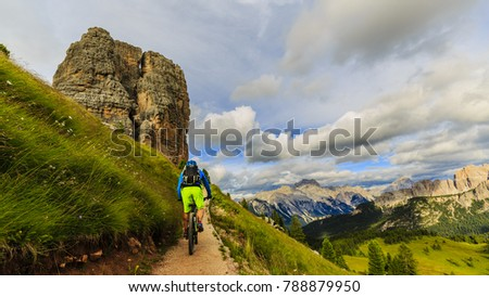 View of cyclist riding mountain bike on single trail in Dolomites, Cinque Torri, South Tirol, Italy #788879950
