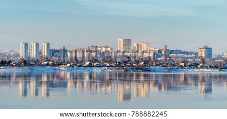 In the mirrored surface of the river Kama, reflects one of the districts of the city of Perm, located on the opposite Bank. Winter. Royalty-Free Stock Photo #788882245