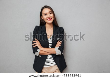 Pleased asian business woman with crossed arms looking at the camera over gray background #788963941