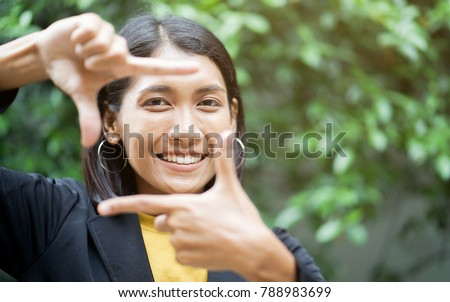 close up asian woman (businesswoman) showing hand as vision symbol frame for look forward to the future with eyesight at outdoor park ,concept for good working business disruption of generation  Royalty-Free Stock Photo #788983699