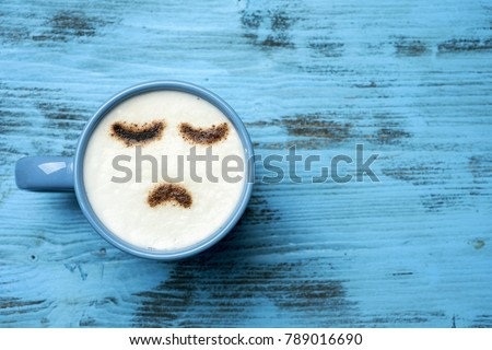 high-angle shot of a blue cup of cappuccino with a sad face drawn with cocoa powder on its milk foam, on a blue rustic table with a blank space on the right #789016690