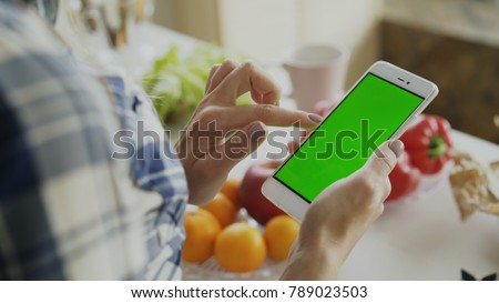 Closeup of woman's hand browsing smartphone with green screen on kitchen at home