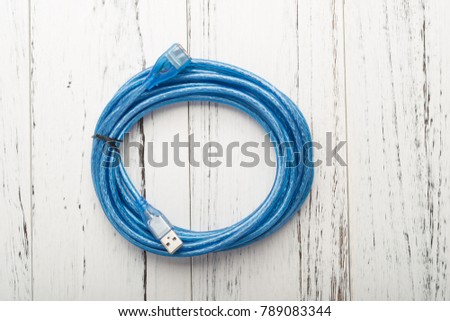 top view blue usb cable on a white wood background #789083344