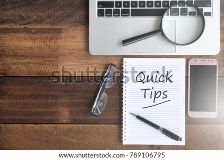 Notebook, smartphone, magnifying glass, spectacles and QUICK TIPS word. quick tips flat lay concept