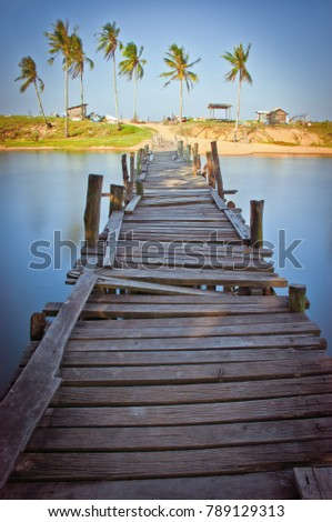 Old antique wooden bridge crossing small river that connect local village to near by beach in Pulau Kerengga, Marang Terengganu. Nature composition (motion soft focus blurry noise grain visible) #789129313