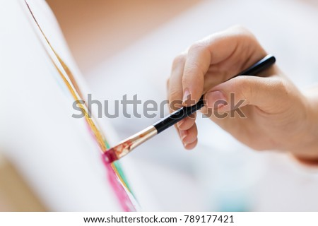 art, creativity and people concept - hand of artist with brush painting picture Royalty-Free Stock Photo #789177421