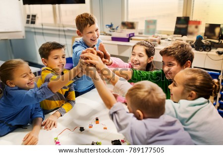 education, children, technology, science and people concept - group of happy kids building robots and making high five gesture at robotics school #789177505