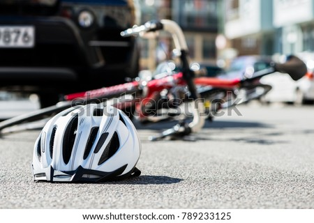 Close-up of a bicycling helmet fallen on the asphalt  next to a bicycle after car accident on the street in the city #789233125