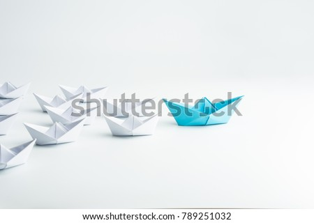 Leadership concept with blue paper ship leading among white #789251032