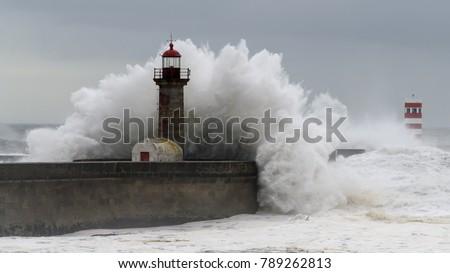 Waves crashing over a lighthouse Royalty-Free Stock Photo #789262813