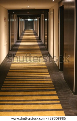View of a dark corridor with leading lines. The space is empty and nobody can be seen. Form as a tunnel with rectangles in perspective. Convergence of lines in the direction of a light at the end.   #789309985