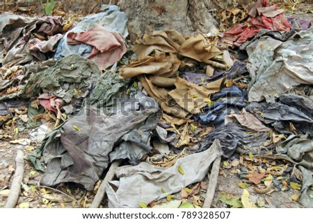 Clothes still lie in the Cambodian Killing Fields as a memorial to the 8985 innocent victims.  #789328507