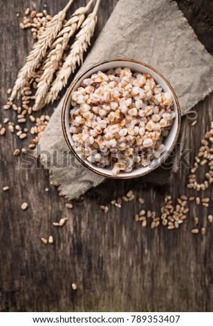 Bowl of barley porridge on wooden background. Top view #789353407