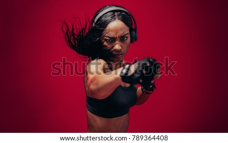 Boxer practicing her punches in a studio. African female boxer practicing boxing against red background. #789364408