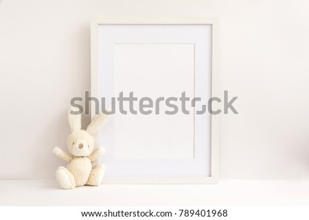 A4 A3 A5 upright white wooden photo frame standing next to wooden toys. Blank photo frame for text or work overlay perfect for blogger or website designer or marketing person.