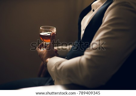 Man holding whiskey glass in hands #789409345