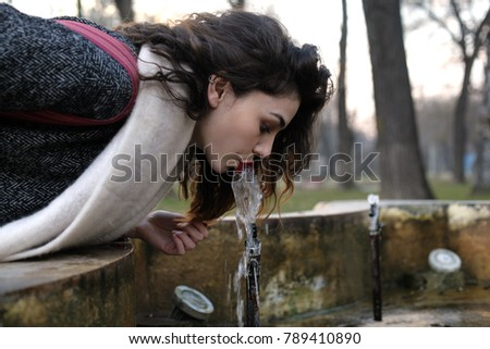 Woman is drinking water from a public fountain. #789410890