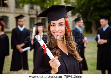 Happy cute brunette caucasian grad girl is smiling, blurred class mates are behind. She is in a black mortar board, with red tassel, in gown, with nice brown curly hair, diploma in hand #789412666