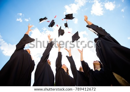 Congratulations! Low angle view of happy group of six young cheerful graduates in black gowns, throwing up their head wear in the air and celebrating, in blue summer sky, laughing, enjoying #789412672