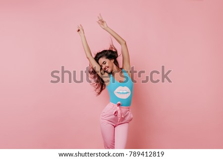 Lovely slim girl posing with sincere smile. Pretty long-haired female model dancing with hands up on pink background. #789412819