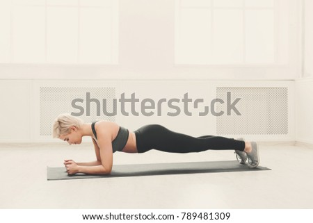 Fitness woman plank workout training at white background indoors. Young slim girl makes exercise. Healthy lifestyle, gymnastics concept #789481309