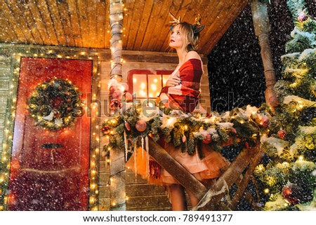 Happy girl in a beautiful dress, wrapped in a blanket, stands near the house decorated for Christmas. Time for miracles. Merry Christmas and Happy New Year. #789491377