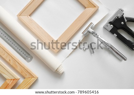 Artist canvas in roll, wooden stretcher bars, canvas stretcher pilers and staple gun. Top view. #789605416